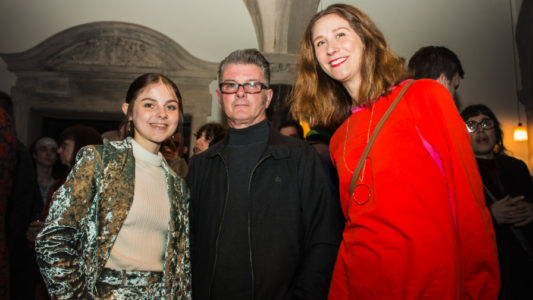 Three people smiling and looking directly at camera. The person on the left is Maisie Murray. She is wearing a white top and velvet jacket. The person is the middle is Maisie's dad Mike. He is wearing glasses and a black jacket. The person on the right is Brighter Sound's Lucy Wallace. She is wearing a red dress.
